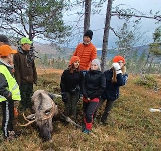De fleste av ungdomsskoleelevene samlet sammen med elgen som ble skutt under jakten. F.v. Aksel Kongsdal (i jaktklær delvis skjult), Sebastian Storesund, Marius Forsmo Sørli, elgen, Sandra Oksfjellelv, Espen Moen (bakerst), Ayla Syversen og Ingvild Holmen.